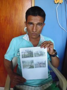 Giovanny Yamid Aldana holds a photo of his home, destroyed during a bombing by the Colombian Air Force on November 24, 2013. Photo by Dawn Paley.